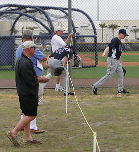 A Rays Fan Holds Up Rope For Pitcher During Practice In Port